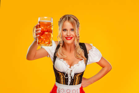 Young sexy Oktoberfest girl waitress, wearing a traditional Bavarian or german dirndl. Woman serving big beer mugs with drink isolated on yellow background.