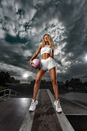 Beautiful and sexy fit woman in outfit with a basketball ball. Sport and sportswear fashion concept
