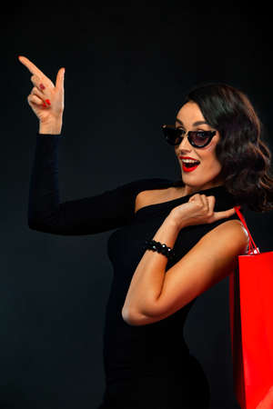 Black Friday sale concept for shop. Girl in sunglasses holding big bag isolated on dark background at shopping. Woman pointing to looking on copy space for sales text. 版權商用圖片