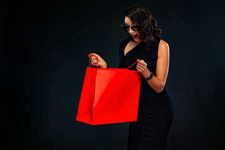 Black Friday sale concept for shop. Surprised woman in sunglasses holding red bag isolated on dark background at shopping. 版權商用圖片