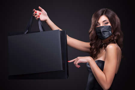 Sale concept in 2020 - time of coronavirus pandemic. . Young smiling woman in medical mask showing shopping bag in black friday holiday. Girl on dark background with copy space 版權商用圖片