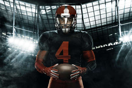 Closeup portrait of american football player, athlete sportsman in red helmet on grand arena background. Sport and motivation wallpaper.