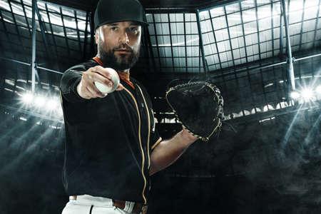 Baseball player with grand arena. Ballplayer on dark background in action. 版權商用圖片