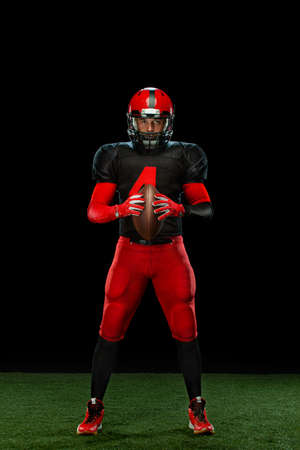 American football player, athlete sportsman in red helmet on black background. Sport and motivation wallpaper.
