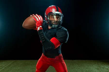 American football player, athlete sportsman in red helmet on dark background. Sport and motivation wallpaper.