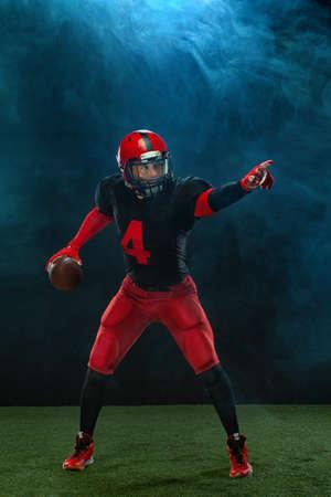 American football player, athlete sportsman in red helmet on dark background with smoke. Sport and motivation wallpaper. 版權商用圖片