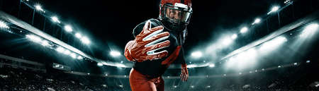 American football player, athlete sportsman in red helmet on stadium background. Sport and motivation wallpaper. Wide photo.