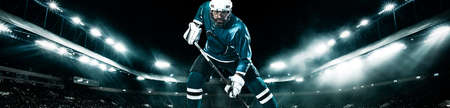 Ice Hockey player athlete in the helmet and gloves on stadium with stick. Action shot. Sport concept. Wide photo.