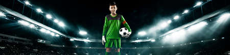 Kids - soccer champion. Boy goalkeeper in football sportswear on stadium with ball. Sport concept. Wide photo.