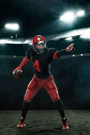 American football player in action, athlete sportsman in red helmet on stadium background. Sport and motivation wallpaper.