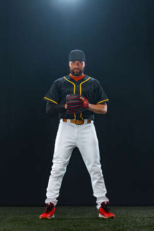 Baseball player on dark background. Ballplayer portrait. Stock Photo