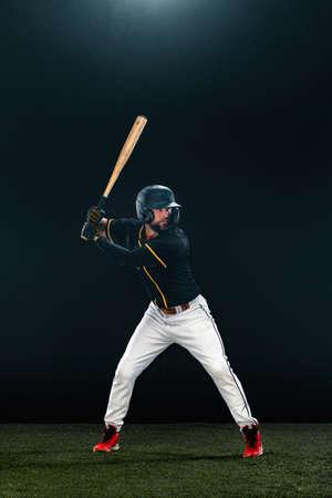 Baseball player with bat on dark background. Ballplayer portrait.