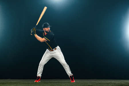 Baseball player with bat on dark background. Ballplayer portrait.