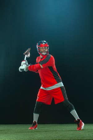 Lacrosse Player, athlete sportsman in red helmet on dark background. Sport and motivation wallpaper.