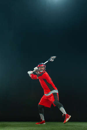 Lacrosse Player, athlete sportsman in red helmet on dark background. Sport and motivation wallpaper.