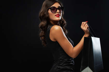 Woman at shopping. Black Friday sale concept for shops. Happy smiling girl in sunglasses holding big bag isolated on dark background at shopping. 版權商用圖片
