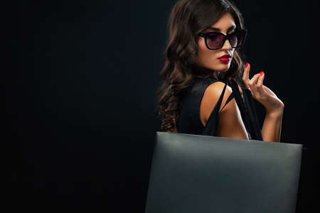 Black Friday sale concept for shops. Shopping woman in sunglasses holding red bag isolated on dark background.
