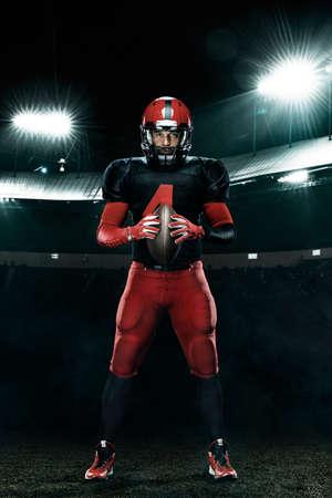 American football player, athlete sportsman in red helmet on stadium background. Sport and motivation wallpaper.
