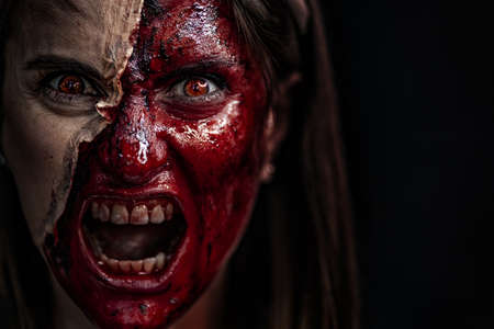 Zombie makeup on Halloween 2020. Creative art make-up for eve of All Saints Day party. Creepy bloody face. Close-up portrait of horrible woman. Horror.