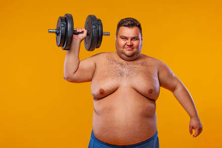 Fat man doing workout traning with dumbbells. Happy guy isolated over yellow background. Stockfoto