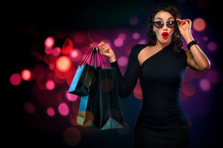 Black Friday sale concept for shop. Shopping woman in sunglasses holding red bag isolated on dark background at shopping on blackfriday.