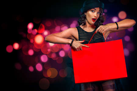 Black friday sale concept for shop. Shopping girl holding red bag isolated on dark background at shopping on blackfriday. Woman pointing to looking left on copy space.