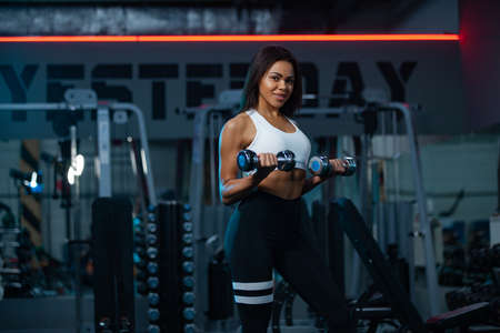 Muscular young fitness sports woman workout with barbell in fitness gym.