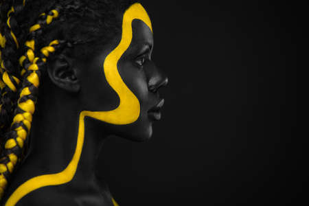 Yellow and black body paint. Woman with face art. Young girl with colorful bodypaint. An amazing afro american model with makeup.