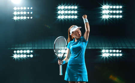 Tennis player with racket in blue costume. Woman athlete playing on grand arena background.