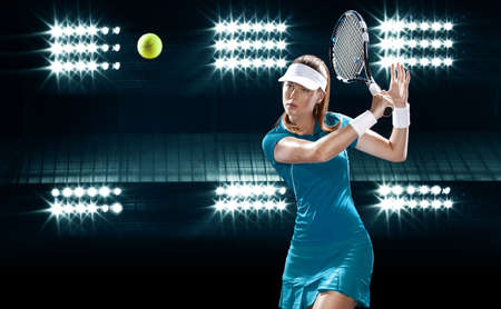 Tennis player with racket in blue sportswear. Woman athlete playing on grand arena background.