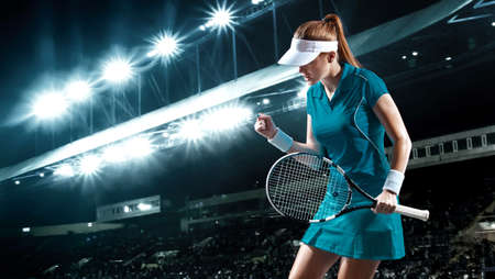 Tennis player with racket. Woman athlete celebrating victory on grand arena background after good play.