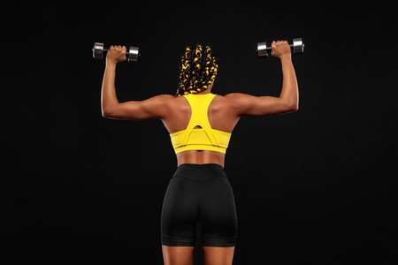 African american woman athlete bodybuilder. Muscular young fitness sports woman workout with dumbbells in fitness gym.