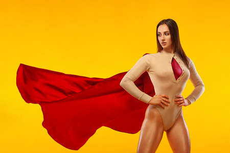 Woman super hero. Sporty fit woman, athlete posing on yellow background.