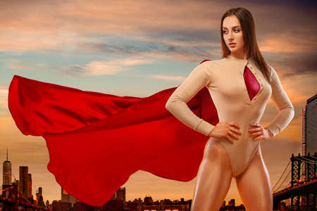 Woman super hero. Sporty fit woman, athlete posing on city background.