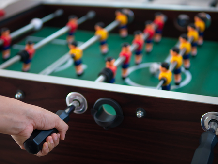 left hand holding the handle to control foosball table
