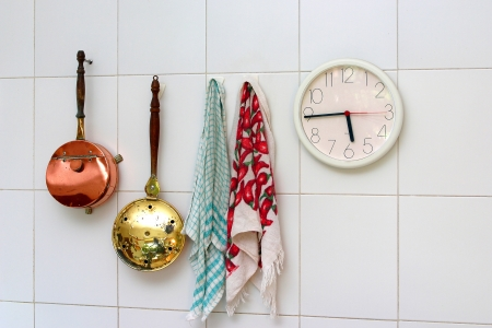kitchen utensils and wall clock hanging on a white tiled wall Stock Photo