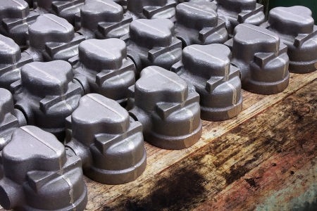 cast metal machine parts displayed in regular pattern