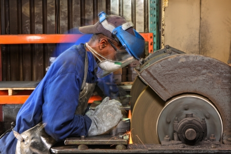 worker in protective clothing grinding a machined part Stock Photo