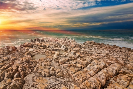 shoreline rocks bathed in golden sunlight against a stormy sea Stock Photo - 16685386
