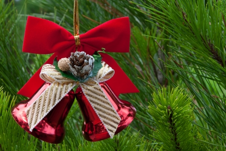 hanging christmas decor of red bells and bow in green tree