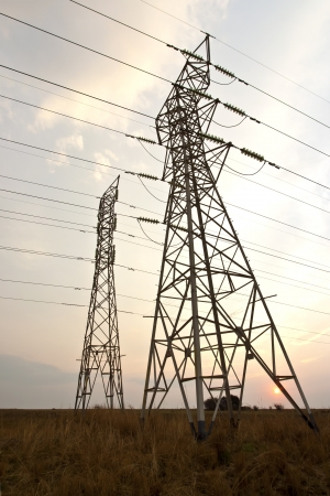 electricity power lines and pylons at sunries or sunset