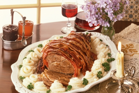 roast leg of lamb with bacon strips in classic setting photo
