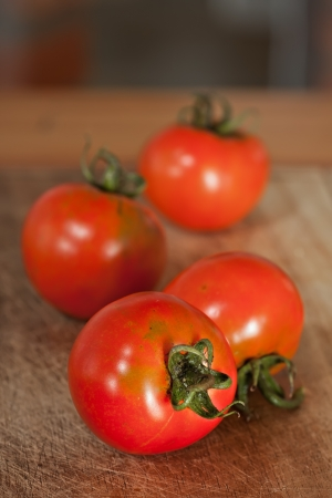 red tomatoes displayed on wooden board