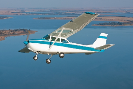 light aircraft in flight over a watery background