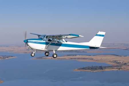 light aircraft flying over a lake level wings Stock Photo