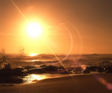 yellow sunrise over sandy beach and ocean waves photo