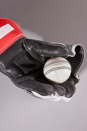 wicket: white cricket ball caught in wicket keepers glove