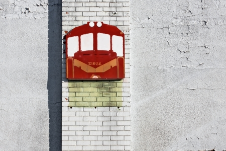 old textured signage of red train on a white brick wall photo