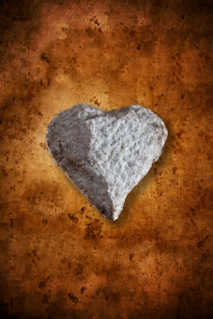 concept of heart of stone, tough love, on a warm textured background