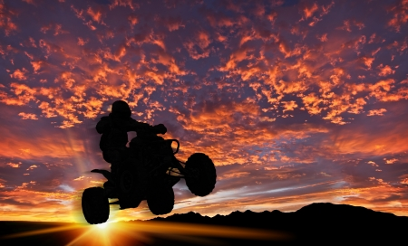 dramatic background sky with quad bike rider silhouetted against setting sun